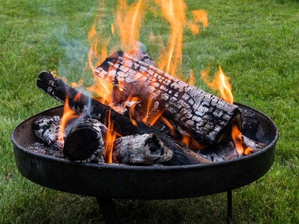 Feuerschale mit Holz und Flammen im Garten, fire bowl with wood and flames in a garden