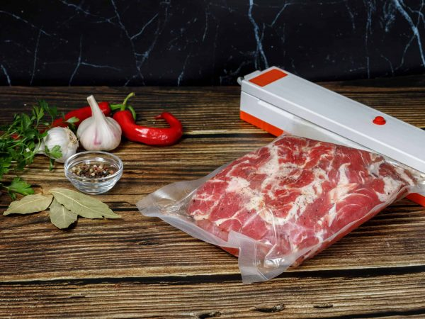 Bagging of meat with a device on the wood surface.